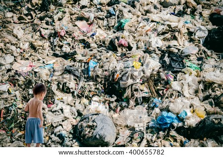 Child and landfill dump site, pollution effect - stock photo