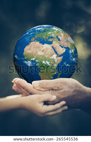 Child and senior holding 3D planet in hands against green spring background. Earth day holiday concept. Elements of this image furnished by NASA