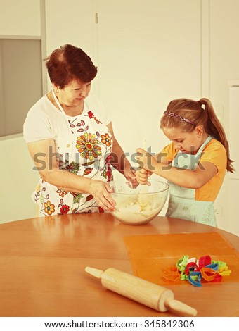 Child and senior woman baking cookies for Christmas in vintage look - stock photo