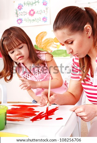 Child and teacher painting at easel in school. - stock photo
