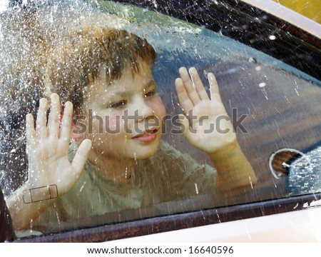 child and window on a wet rainy day ... - stock photo