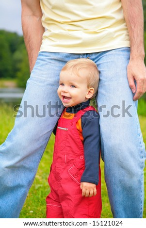 child at legs of father