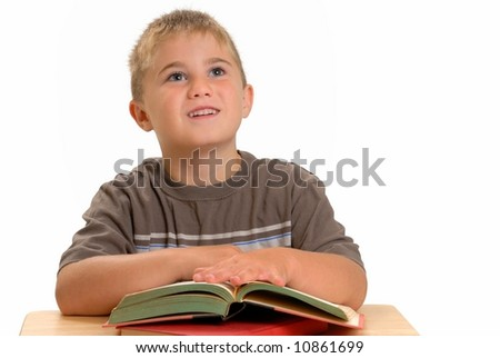 Child at school desk with books - stock photo