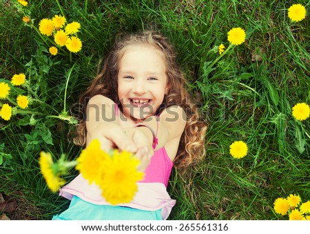 Child at summer. Happy girl outdoors on green grass - stock photo
