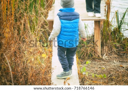 Child at the river, autumn, fishing rod