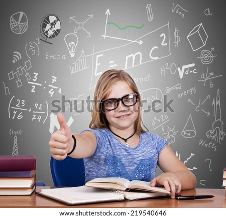 child at the table with books and school terms - stock photo