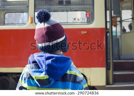 Child at tram or bus stop waiting door to open, tram with open door in the background, back view.