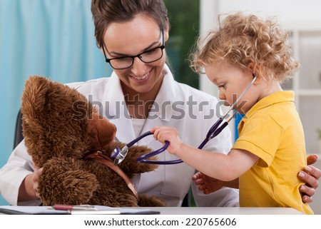 Child auscultating teddy bear at pediatrician's office - stock photo