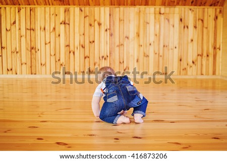 Child baby toddler crawling facing backwards from the back rear on a wooden background. Place for text. - stock photo