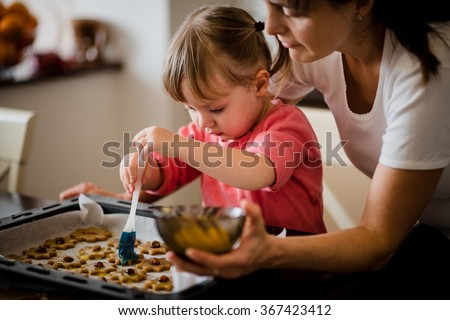 Child baking cookies together with her mother - painting honey cakes with egg yolk - stock photo