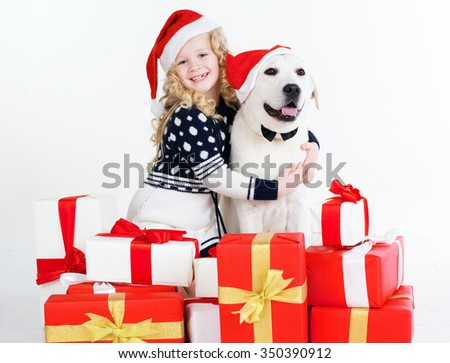 Child blonde girl with white labrador dog are wearing christmas hats. Happy child. Studio shot - stock photo
