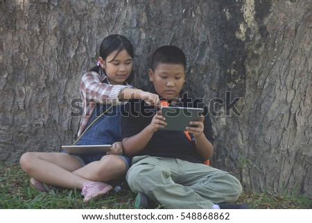child boy and girl playing with tablet at garden