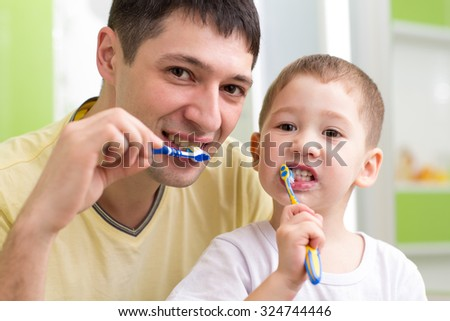 child boy and his father brushing teeth in bathroom - stock photo
