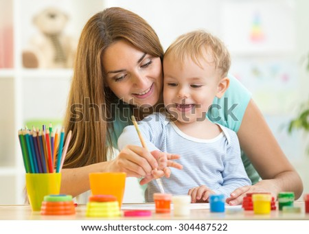 child boy and woman painting in daycare or nursery or playschool - stock photo