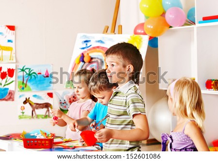 Child boy cutting out scissors paper in preschool. - stock photo