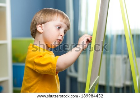 Child boy draws on chalkboard - stock photo