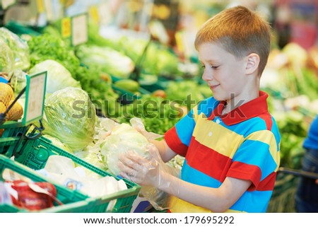 child boy during shopping with cabbage vegetable at supermarket - stock photo