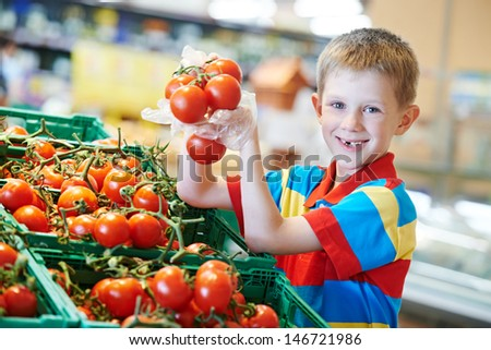 child boy during shopping with red ripe tomato vegetables at supermarket - stock photo
