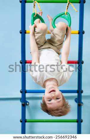 child boy hanging on gymnastic rings at home - stock photo
