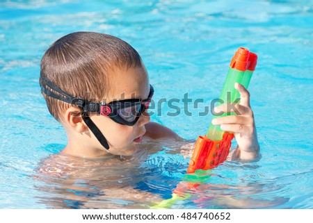 Child boy in swimming pool playing with a water gun
