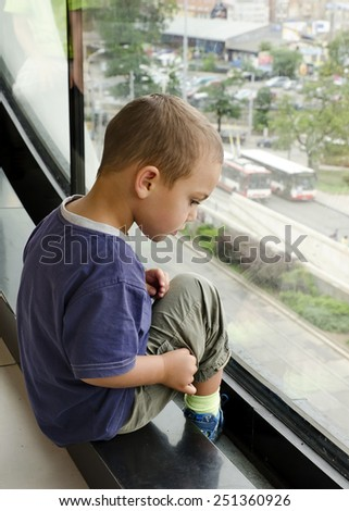 Child boy looking from a large window, watching traffic on a street below. - stock photo