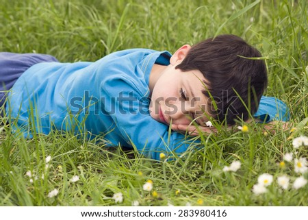 Child boy lying in grass resting and relaxing with closed eyes