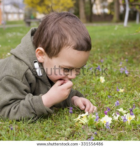 Child boy lying on grass, exploring spring flowers