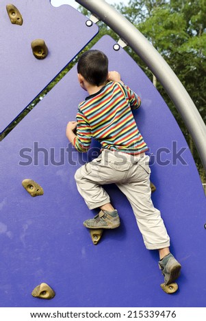 Child boy on a climbing wall at children outdoor playground.  - stock photo