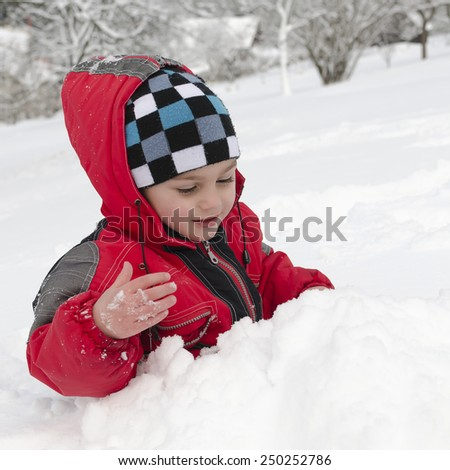 Child boy playing in a fresh deep snow in winter.
