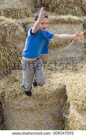 Child boy playing in hay, jumping from a haystack