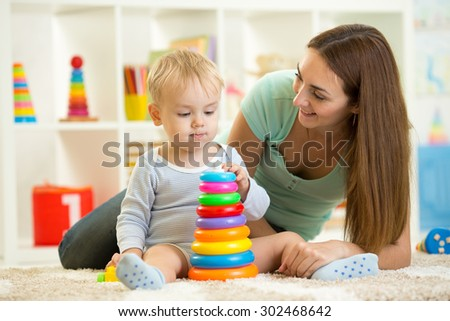 child boy playing together in nursery at home - stock photo