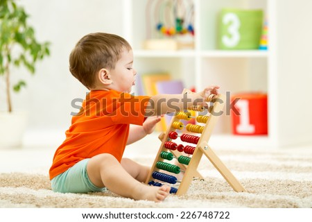 child boy playing with counter toy at home - stock photo