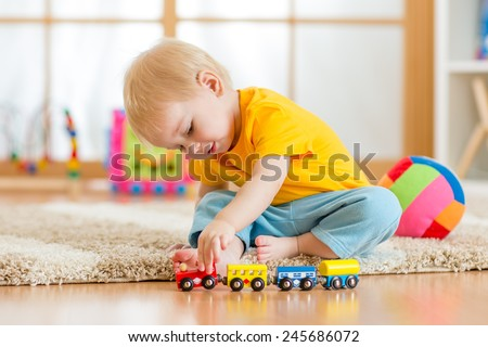 child boy playing with toys indoors at home - stock photo
