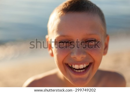 child boy portrait close up sunset backlight happy laughing braces teeth selective focus - stock photo