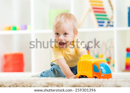 child boy toddler playing with toy car at home - stock photo