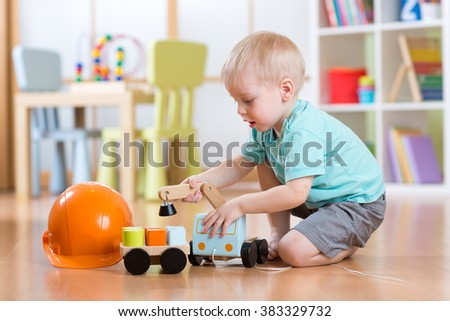 child boy toddler playing with toy car indoors - stock photo