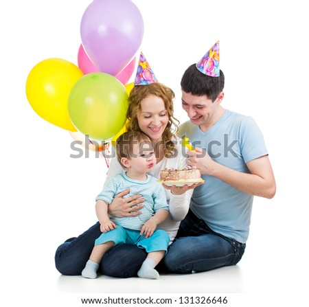 child boy with parents celebrating birthday  and blowing candles on cake - stock photo