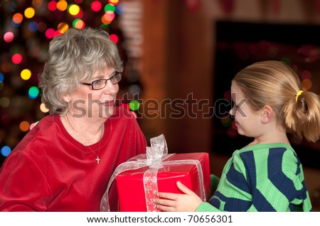 Child bringing Christmas present to Grandmother with tree - stock photo