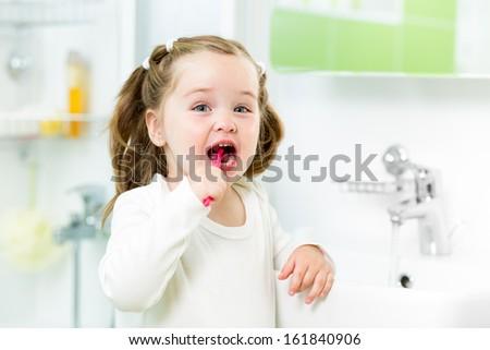 child brushing teeth in bathroom - stock photo