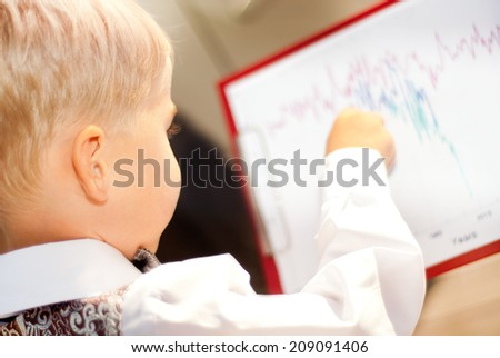 child businessman studying blueprints on the planchette - stock photo