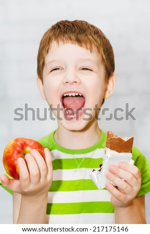 Child chooses chocolate or apple on a light background in the studio. - stock photo