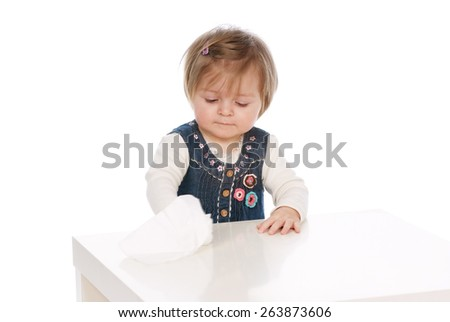 Child cleans Baby wipes white table - stock photo