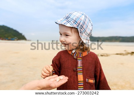 Child collecting pebbles and shells and giving them to her mother on a tropical sandy beach in the summer. Parenthood and childhood concept.  - stock photo