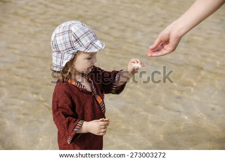 Child collecting pebbles and shells and showing them to her mother on a tropical sandy beach in the summer. Parenthood and childhood concept.  - stock photo