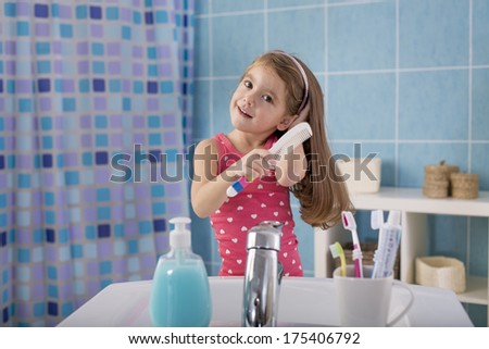 Child comb her hair in the bathroom - stock photo