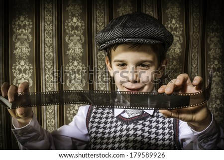 Child considered analog photographic film. Vintage clothes and background - stock photo