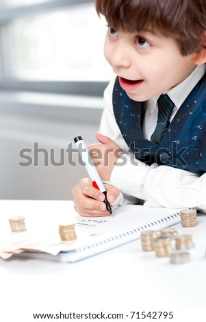 Child counting money and taking notes. Selective focus on the notebook. - stock photo