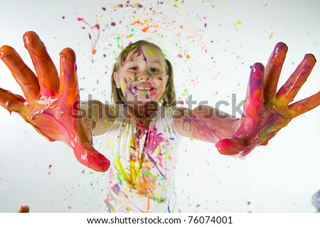 Child covered in colorful paint showing her hands