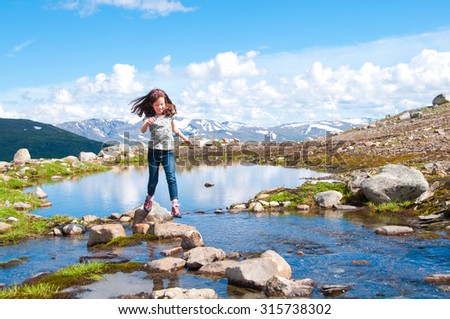Child crossing mountain lake in Norway - stock photo