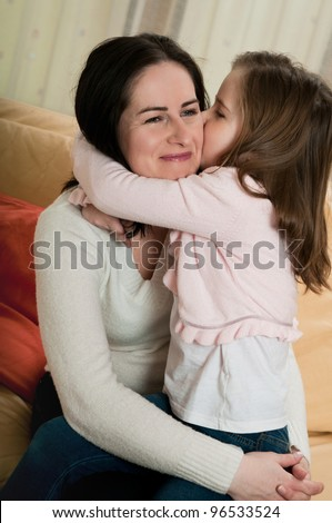 Child (cute ligirl) kissing her mother - indoors at home - stock photo